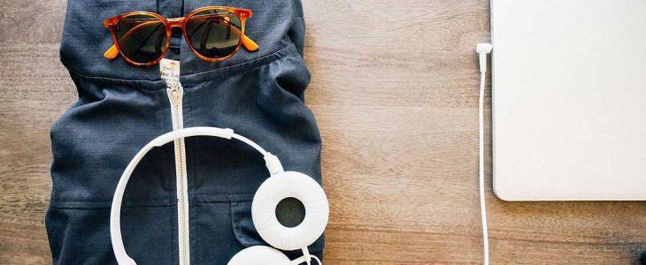 Photo d'un bureau avec un ordinateur et une veste avec lunette de soleil et casque audio.