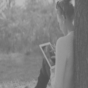 Photo d'une femme sur sa Tablette contre un arbre.
