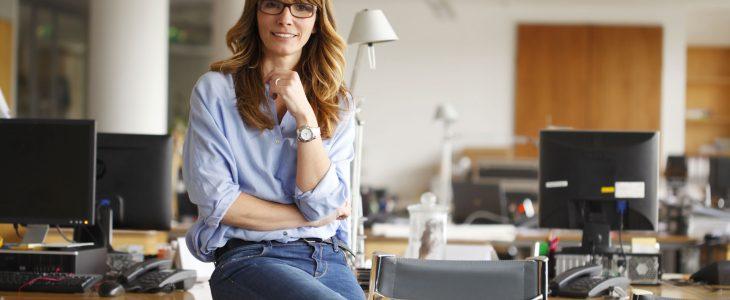 Photo d'une femme assise sur un bureau.